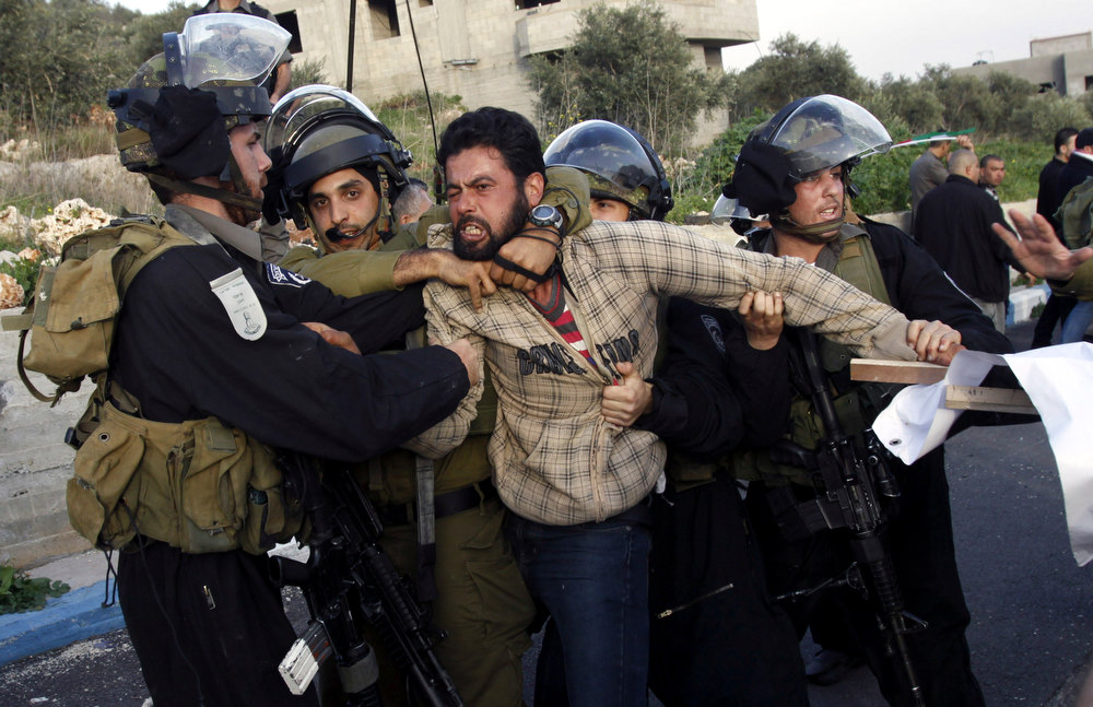 Description of . Israeli security forces detain a Palestinian during clashes in the West Bank village of Anin, Saturday, Jan. 26, 2013. Hundreds of Palestinians clashed with Israeli security during a rally in support of Palestinians in Israeli jails. (AP Photo/Mohammed Ballas)