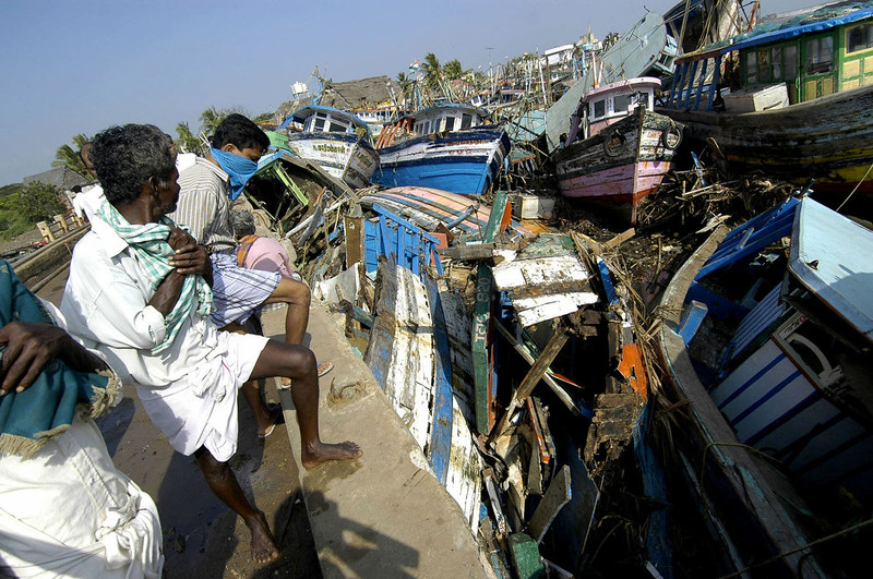 . Indian fishermen survey the devastation of damaged fishing boats in the port of Nagapattinam  some 350 km south of Madras, 28 December 2004, after tidal waves hit the region.   The death toll in India from giant tidal waves that crashed into the coasts of Asia has crossed 7,500 with tens of thousands of people missing, officials said.  The death toll of 7,523 included 3,000 in the Andaman and Nicobar Islands, close to the epicenter of the Indonesian earthquake that caused the tsunamis, and another 4,500 in the southern Indian state of Tamil Nadu and the former French colony of Pondicherry, officials and the Press Trust of India said. AFP PHOTO/Prakash SINGH