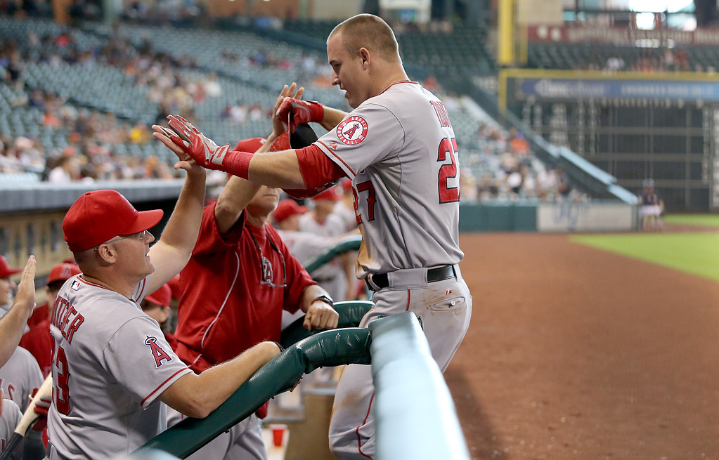 . HOUSTON, TX- SEPTEMBER 15: Mike Trout #27 of the Los Angeles Angels of Anaheim high fives teammates after scoring against the Houston Astros in the first inning on September 15, 2013 at Minute Maid Park in Houston, Texas. (Photo by Thomas B. Shea/Getty Images)