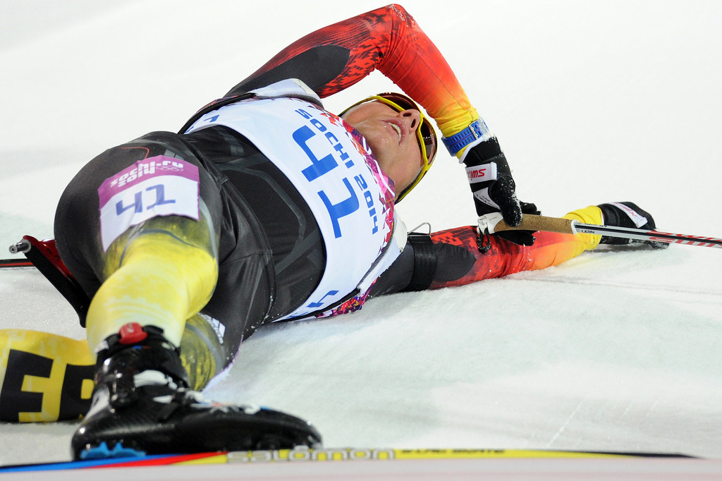 . Silver medalist Germany\'s Erik Lesser lies on the snow after crossing the finish line in the Men\'s Biathlon 20 km Individual at the Laura Cross-Country Ski and Biathlon Center during the Sochi Winter Olympics on February 13, 2014 in Rosa Khutor near Sochi.  KIRILL KUDRYAVTSEV/AFP/Getty Images