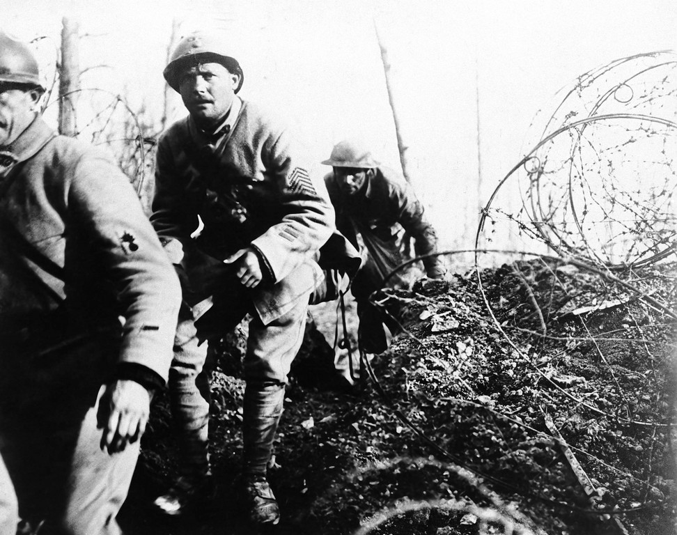 . Two Frenchmen (in foreground) and an American soldier of the 168th infantry (originally Iowa National guardsman) coming over the top with sacks of hand grenades to harass the enemy in a French raid in 1919. (AP Photo)