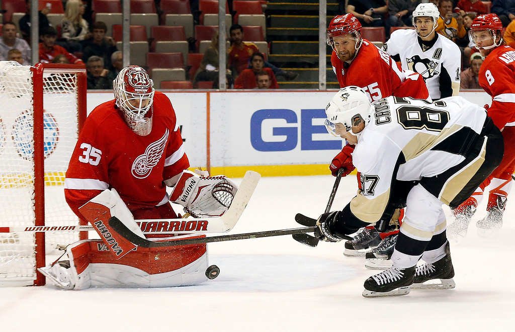 . Detroit Red Wings goalie Jimmy Howard (35) stops a shot by Pittsburgh Penguins\' Sidney Crosby (87) in the third period of a NHL preseason hockey game in Detroit Wednesday, Oct. 1, 2014. (AP Photo/Paul Sancya)