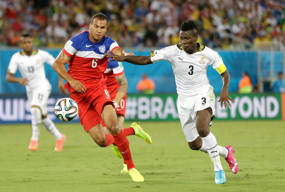 . United States\' John Brooks, left, challenges Ghana\'s Asamoah Gyan for the ball during the group G World Cup soccer match between Ghana and the United States at the Arena das Dunas in Natal, Brazil, Monday, June 16, 2014. (AP Photo/Ricardo Mazalan)