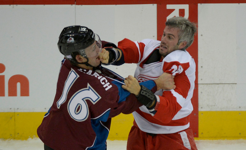 . Colorado Avalanche defenseman Cory Sarich (16) gets hit by Detroit Red Wings left wing Drew Miller (20) during a fight in the second period  October 17, 2013 at Pepsi Center.(Photo by John Leyba/The Denver Post)
