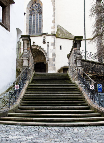 Stairs on a cobblestone street lead to church entrance