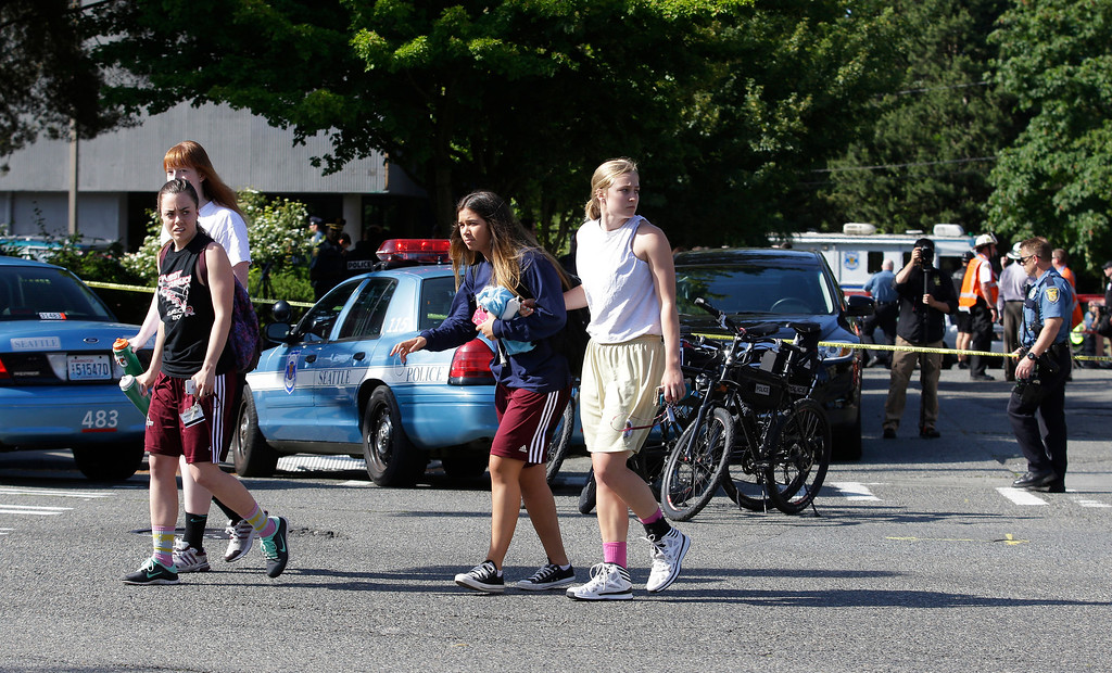 . Students help each other as they walk away from the scene of a shooting Thursday, June 5, 2014, at Seattle Pacific University in Seattle. Police say a university student on Thursday disarmed a lone gunman who entered a building and shot four people. A hospital spokeswoman says one man has died and three other people are injured, one critically. (AP Photo/Ted S. Warren)