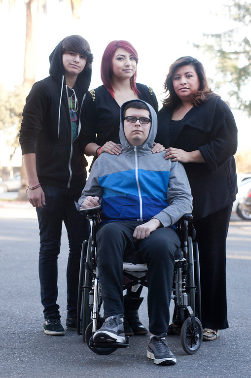 . Everett Zamarron-Smith, foreground, with his family, from left, brother, Coady, 13, sister, Lakien,19, and mother, Delva, outside the Valley Medical Center rehabilitation center in San Jose Thursday, Jan. 3, 2013. When Everett Zamarron-Smith tumbled off his skateboard last June, everything changed. The 16-year-old Gilroy High School student suffered a traumatic brain injury and today is making slow progress in the arduous process of reclaiming his life. (Patrick Tehan/Staff)
