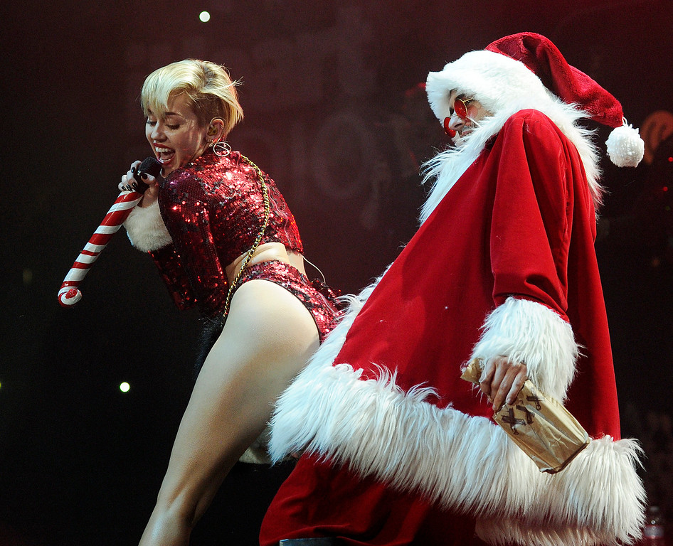. Miley Cyrus, left, performs alongside a dancer dressed as Santa Claus during the KIIS-FM Jingle Ball concert at Staples Center, on Friday, Dec. 6, 2013, in Los Angeles. (Photo by Chris Pizzello/Invision/AP)