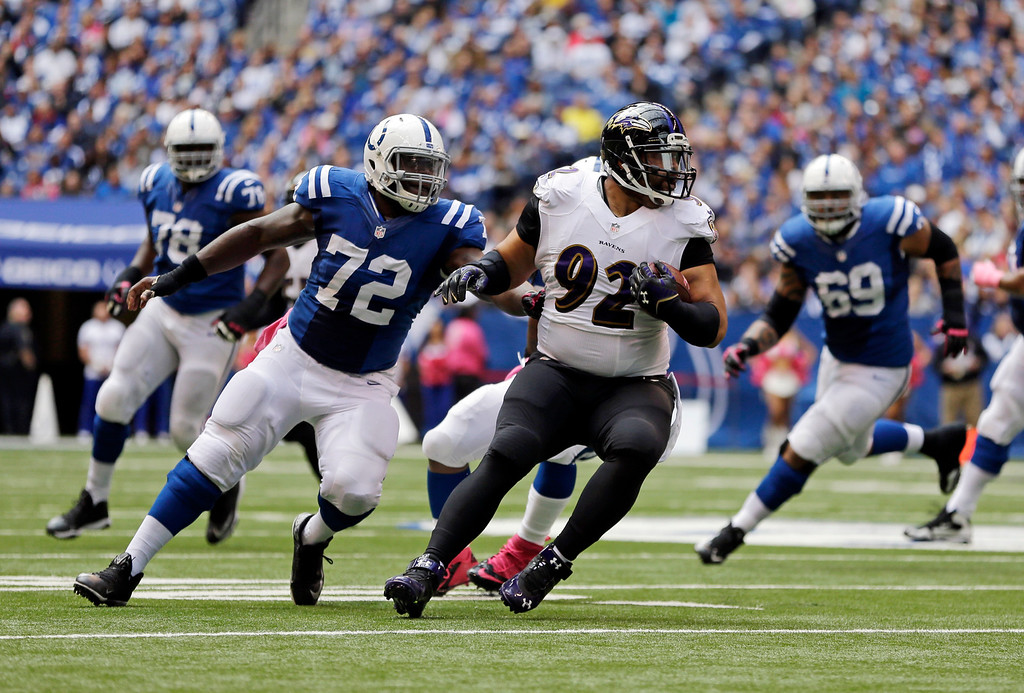 . Baltimore Ravens nose tackle Haloti Ngata, right, is chased by Indianapolis Colts center Jonotthan Harrison after intercepting a pass during the first half of an NFL football game in Indianapolis, Sunday, Oct. 5, 2014. (AP Photo/Jeff Roberson)