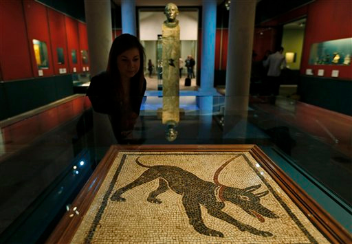 . A British Museum employee poses for the photographers in front of a mosaic panel (emblema) depicting a guard dog that was found in Pompeii, during a photo call for the upcoming exhibition entitled \'Life and death Pompeii and Herculaneum\', in central London, Tuesday, March 26, 2013. The exhibition about the two Roman cities, buried by a catastrophic volcanic eruption of Mount Vezuvius in 79 AD, will run at the museum from March 28 to Sept. 29, 2013. (AP Photo/Lefteris Pitarakis)
