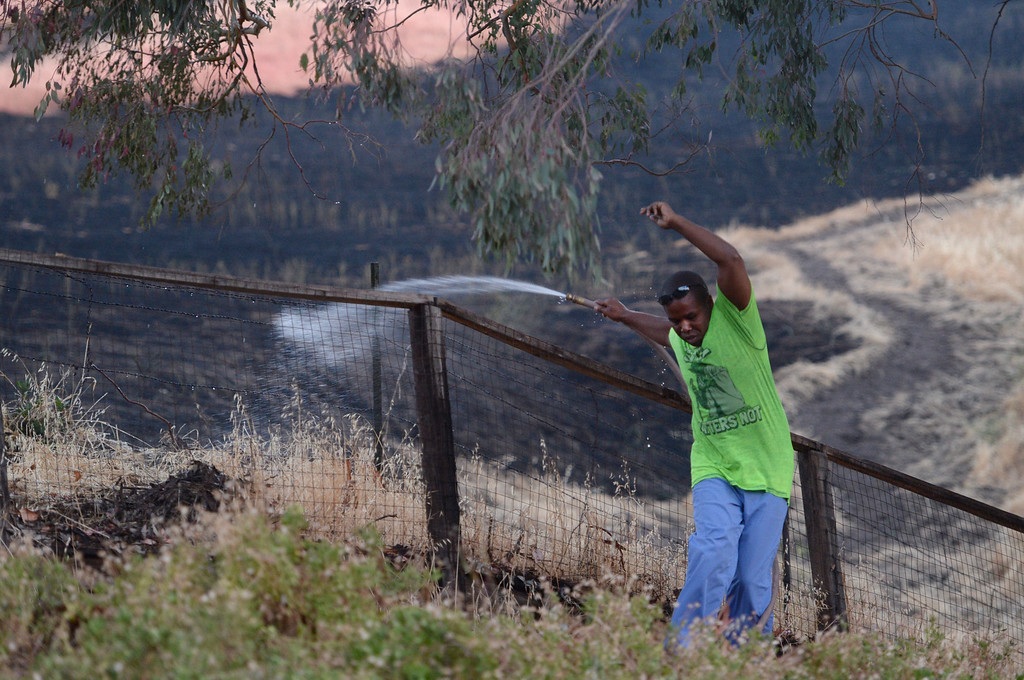 . Nicholas Quinn tries to keep his balance as he sprays down the burned open space between his home and his backyard along Grimsby Drive in Antioch, Calif., on Wednesday, June 24, 2015. Quinn was home at the time studying for a podiatrist exam when a neighbor knocked on his door and told him about the fire. He immediately started spraying down an area where one of his backyard trees hangs over the fence. A fire break can be seen at right where firefighters carved a path in the hillside to stop the fire from getting to homes. Quinn was one of many evacuated from his home in the area where the fire came really close. (Susan Tripp Pollard/Bay Area News Group)
