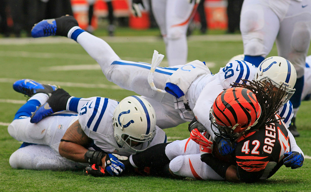 . Cincinnati Bengals running back BenJarvus Green-Ellis (42) is tackled by Indianapolis Colts strong safety LaRon Landry (30) and inside linebacker Jerrell Freeman (50) in the first half of an NFL football game on Sunday, Dec. 8, 2013, in Cincinnati. (AP Photo/Tom Uhlman)
