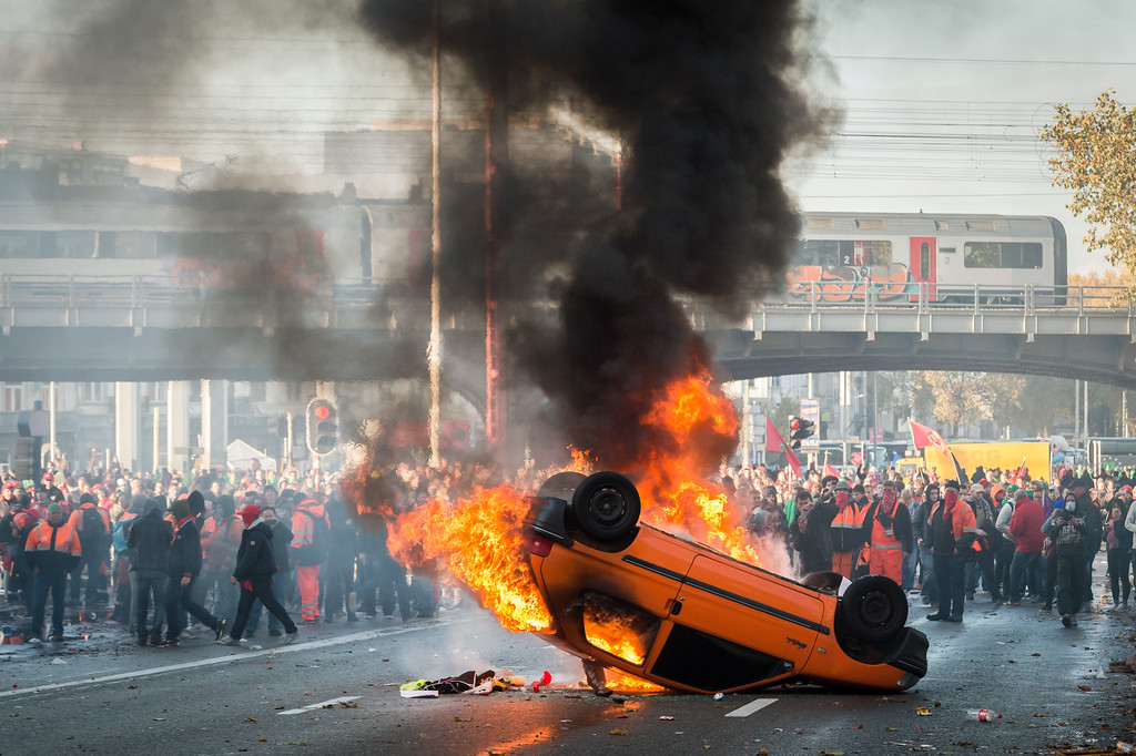 . Protestors stand behind a burning car during a national trade union demonstration in Brussels, Thursday Nov. 6, 2014. (AP Photo/Geert Vanden Wijngaert)