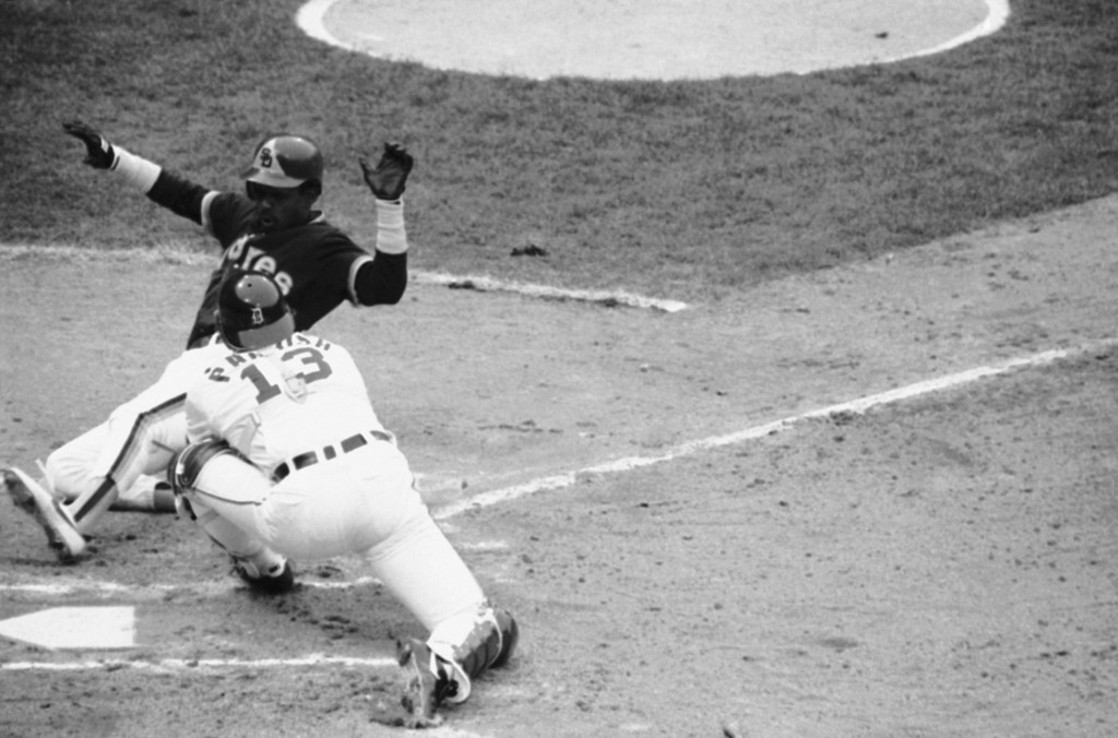 . Alan Wiggins is cut down at the plate, sliding wide, as Tiger catcher Lance Parrish (13) reaches to try to tag the Padre runner in the first inning of the World Series, Sunday, Oct. 14, 1984, Detroit, Mich. Parrish had to apply a second tag. (AP Photo/Lenny Ignelzi)