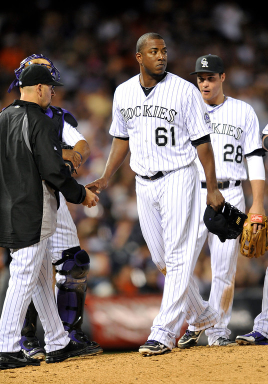 . Colorado Rockies relief pitcher Edgmer Escalona (61) looks on as he hands the ball to manager Walt Weiss after giving up two runs to the San Francisco Giants during the seventh inning of a baseball game on Friday, May 17, 2013, in Denver. (AP Photo/Jack Dempsey)