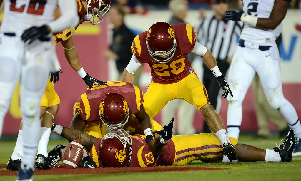 . USC\'s  Tre Madden #23 is surrounded by teammates after hauling in a touchdown pass during their game against Arizona at the Los Angeles Memorial Coliseum Thursday, October 10, 2013. (Photo by Hans Gutknecht/Los Angeles Daily News)