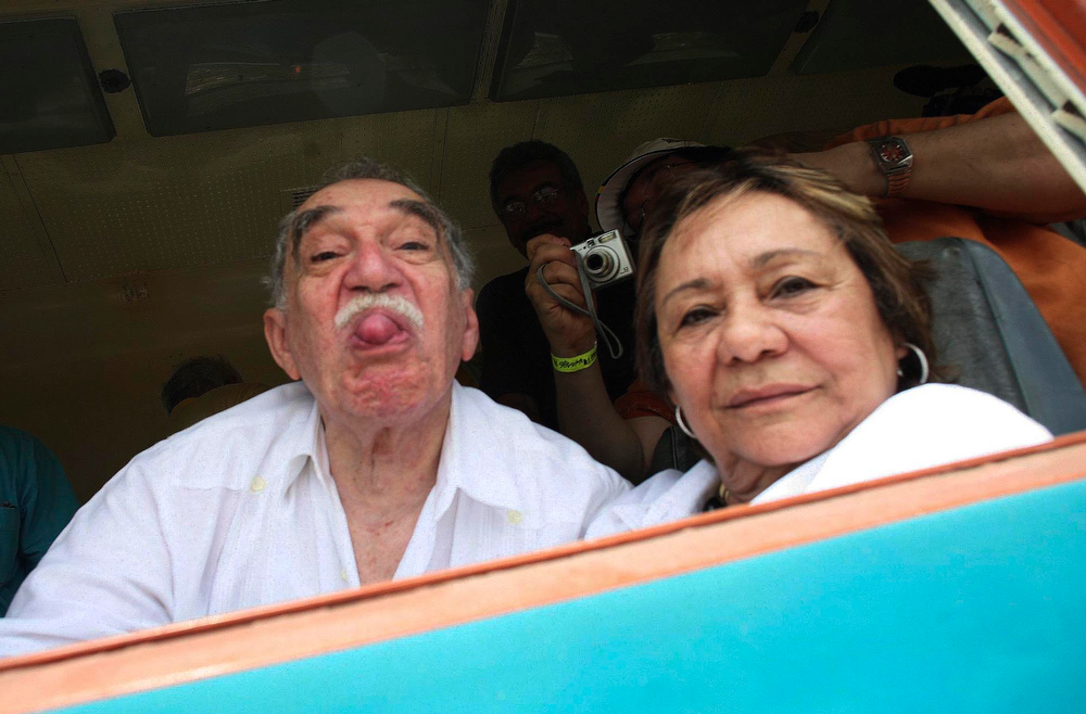 . In this May 30, 2007 file photo,  Colombia\'s Literature Nobel Prize winner Gabriel Garcia Marquez sticks out his tongue to photographers upon his arrival on a train to Aracataca, his hometown in northeastern Colombia.  At right is his wife Mercedes Barcha who accompanied the writer on his first visit to his hometown in 25 years. Marquez died Thursday April 17, 2014 at his home in Mexico City. (AP Photo/William Fernando Martinez, File)