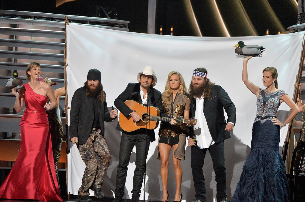 . NASHVILLE, TN - NOVEMBER 06:  \'Duck Dynasty\' performs onstage with Hosts Brad Paisley and Carrie Underwood during the 47th annual CMA Awards at the Bridgestone Arena on November 6, 2013 in Nashville, Tennessee.  (Photo by Rick Diamond/Getty Images)