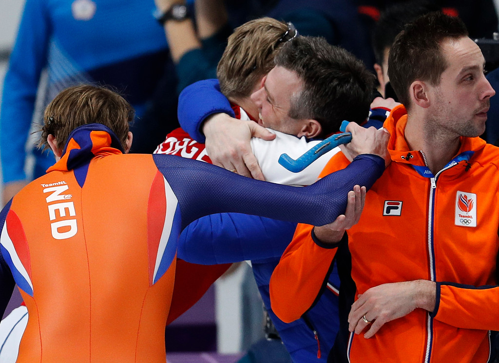 . Gold medalist and new Olympic record holder Havard Lorentzen of Norway hugs his coach, center, as Ronald Mulder of The Netherlands, left, leans on his coach after the men\'s 500 meters speedskating race at the Gangneung Oval at the 2018 Winter Olympics in Gangneung, South Korea, Monday, Feb. 19, 2018. (AP Photo/John Locher)