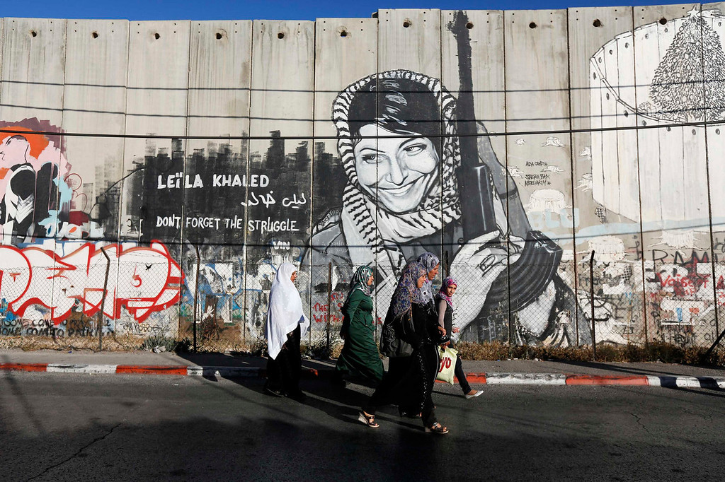 . Palestinian women walk past graffiti on Israel\'s controversial barrier as they walk towards an Israeli checkpoint in the West Bank town of Bethlehem, during the holy month of Ramadan July 26, 2013.  REUTERS/Baz Ratner