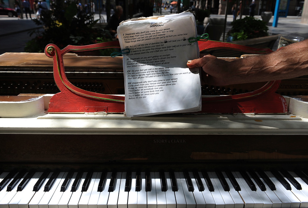 """. Visit with the many piano players that  play the pianos that are along 16th Street Mall in downtown Denver on Tuesday, July 19, 2011.  Clell Golding pulls his lyrics to \""""Desperado\""""  after playing at  Glenarm and 16th Street. Cyrus McCrimmon, The Denver Post"""