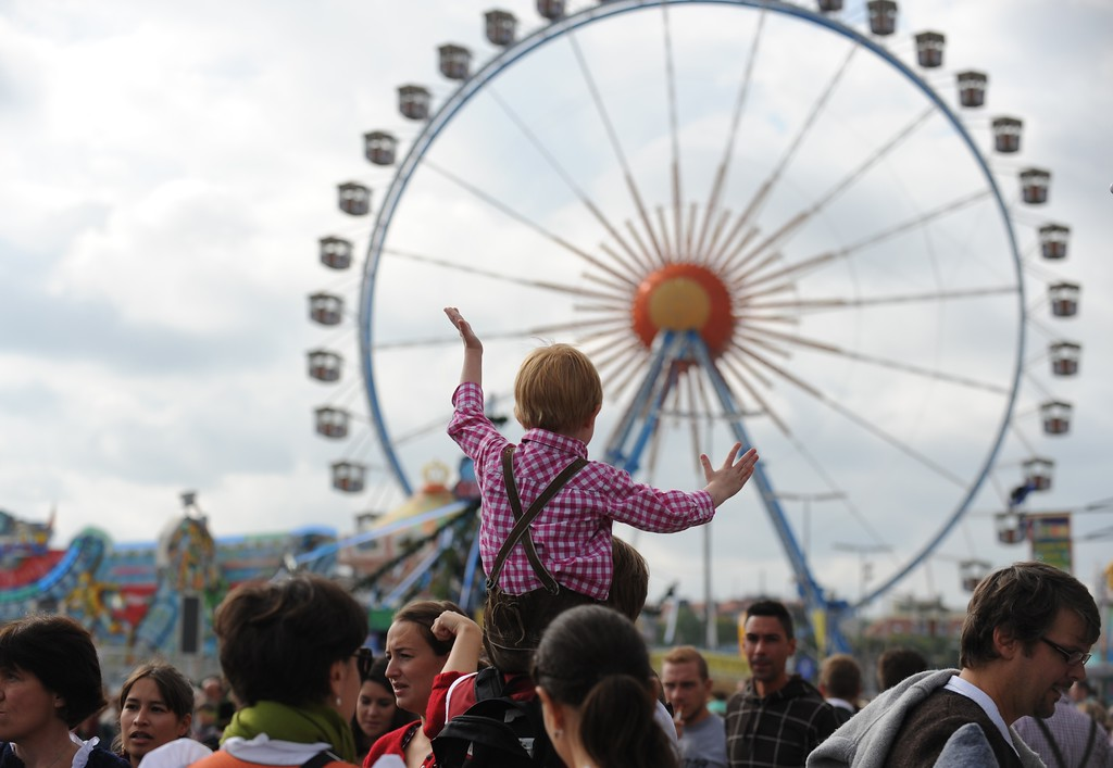. A little boy dressed in traditional Bavarian clothes sits on his father\'s shoulders and reacts as he sees the ferris wheel at the Oktoberfest beer festival at the Theresienwiese in Munich, southern Germany on September 21, 2013. The traditional Bavarian beer festival runs from September 21 - October 6, 2013.  AFP PHOTO / DPA/ ANDREAS GEBERT/AFP/Getty Images