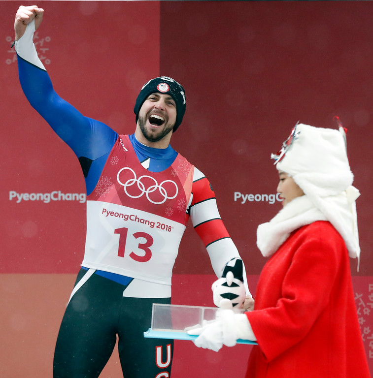 . Chris Mazdzer of United States shouts after getting a toy tiger for taking the silver medal during the winner\'s ceremony of the men\'s luge competition at the 2018 Winter Olympics in Pyeongchang, South Korea, Sunday, Feb. 11, 2018. (AP Photo/Andy Wong)