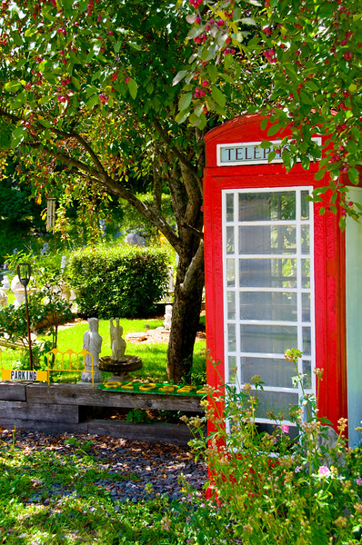 A British-style phone booth lurking near a quaint garden of statues.