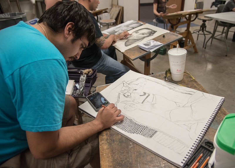 Student Trenton Oliver works on his portriat of his dog.