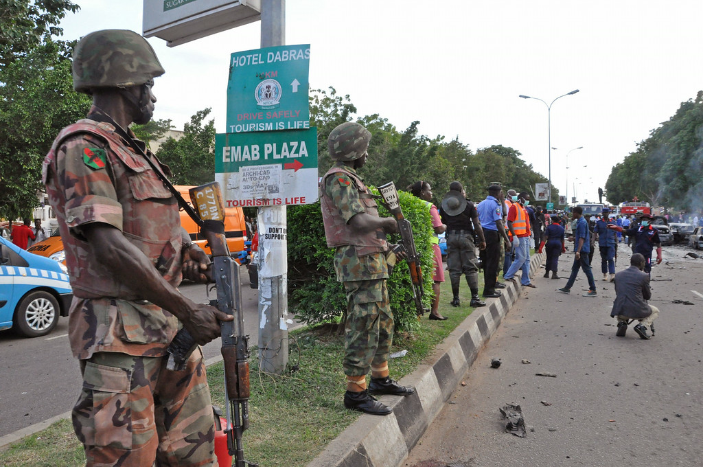 . Members of the Nigerian armed forces, left, stand guard, at the scene of an explosion in Abuja, Nigeria, Wednesday, June 25, 2014.  (AP Photo/Olamikan Gbemiga)