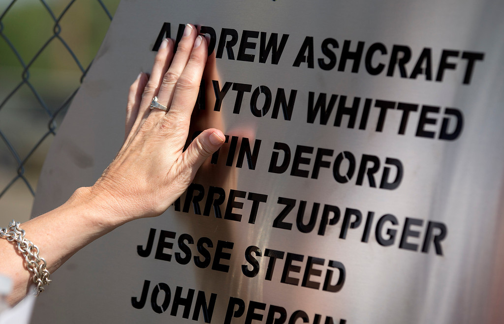 . Linda Lambert places her hand across a plaque hanging on the fence outside the Granite Mountain Interagency Hotshot Crew fire station, Tuesday, July 2, 2013 in Prescott, Ariz.  The plaque holds the names of the 19 firefighters killed Sunday, by an out-of-control blaze near Yarnell, Ariz.  Lambert is the aunt of firefighter Andrew Ashcraft. (AP Photo/Julie Jacobson)
