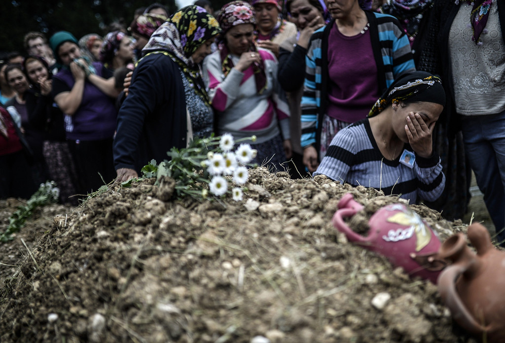 . Duygu Colak, reacts as she sits in front of her husband Ugur\'s grave during a funeral ceremony in the western town of Soma in the Manisa province on May 15, 2014. Turkey\'s four biggest unions will hold a one-day protest strike as anger over the country\'s worst mining accident mounts, with 282 workers confirmed dead and scores still trapped underground. AFP PHOTO/BULENT KILIC/AFP/Getty Images