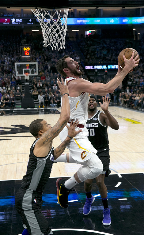 . Cleveland Cavaliers forward Kevin Love, center goes to the basket between Sacramento Kings\' George Hill, left, and Zach Randolph during the first quarter of an NBA basketball game, Wednesday, Dec. 27, 2017, in Sacramento, Calif. (AP Photo/Rich Pedroncelli)