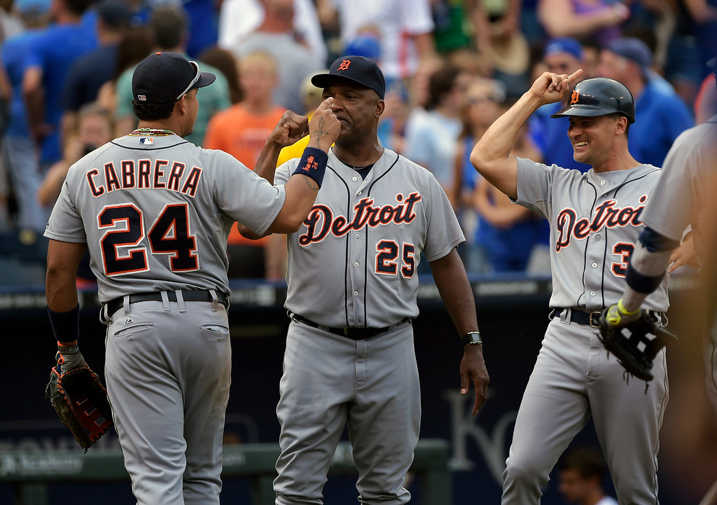 . Detroit Tigers first baseman Miguel Cabrera (24) is congratulated by Detroit Tigers third base coach Dave Clark (25) and Detroit Tigers first base coach Omar Vizquel (31) after defeating the Kansas City Royals in a baseball game Saturday, Sept. 20, 2014, in Kansas City, Mo. (AP Photo/Reed Hoffmann)