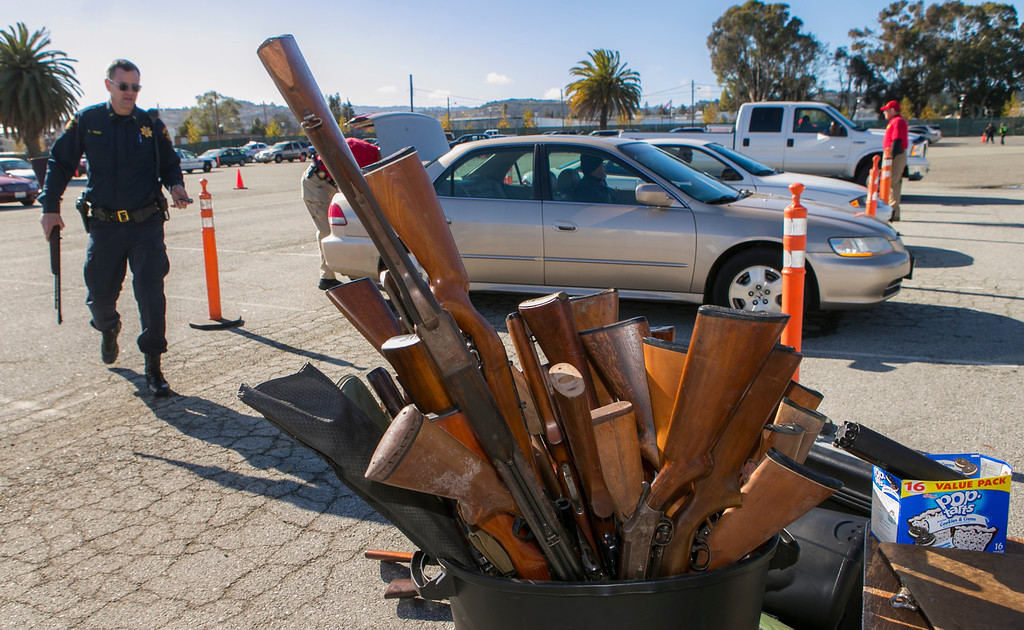 . Tim Reid, left, with the San Mateo County Sheriff\'s office, carries one of the many guns that were turned in during an anonymous gun buyback at the San Mateo County Event Center in San Mateo, Calif., on Saturday, Jan. 26, 2013. Congresswoman Jackie Speier (D-San Francisco/San Mateo), San Mateo County Supervisor Adrienne Tissier and San Mateo County Sheriff Greg Munks held the gun buy back, offering up to $100 cash for a hand gun, shotgun or rifle, and up to $200 cash for an assault weapon. (John Green/Staff)