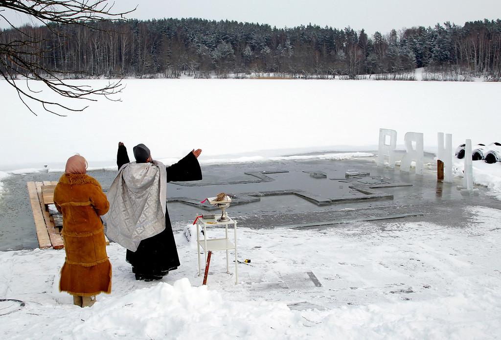 . An Orthodox priest conducts a service at the ice hole of a lake on the eve of Russian Orthodox Epiphany near the village of Pilnitsa, on the outskirts of Minsk, Belarus, Saturday, Jan. 18, 2014. Orthodox Church believers celebrate Epiphany on Jan.19. (AP Photo/Sergei Grits)