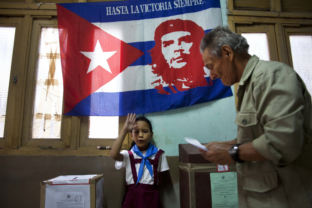 ". Under a Cuban flag with an image of the Argentinean born Cuban revolution leader Ernesto ""Che\"" Guevara, a Cuban schoolgirl raises her hand confirming a voter is properly casting his ballot  at a polling station during parliament elections in Havana, Cuba, Sunday, Feb. 3, 2013. More than 8 million islanders are eligible to vote and will approve 612 members of the National Assembly and over 1,600 provincial delegates.(AP Photo/Ramon Espinosa)"