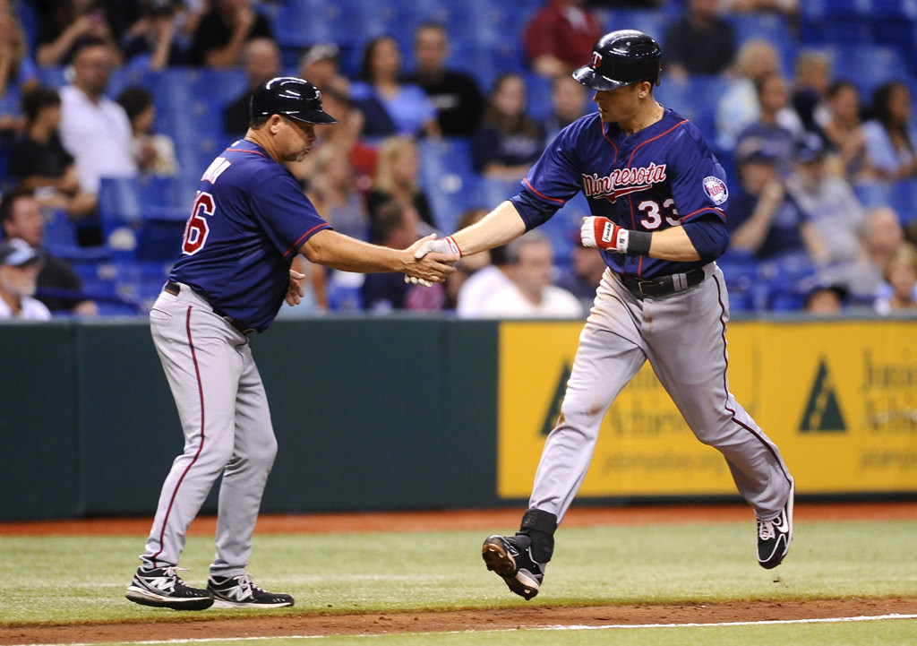 . Minnesota Twins\' Justin Morneau, right, celebrates with third base coach Joe Vavra as he rounds the bases after hitting a solo home run off of Tampa Bay Rays starting pitcher Roberto Hernandez during the fourth inning of a baseball game Monday, July 8, 2013, in St. Petersburg, Fla. (AP Photo/Brian Blanco)