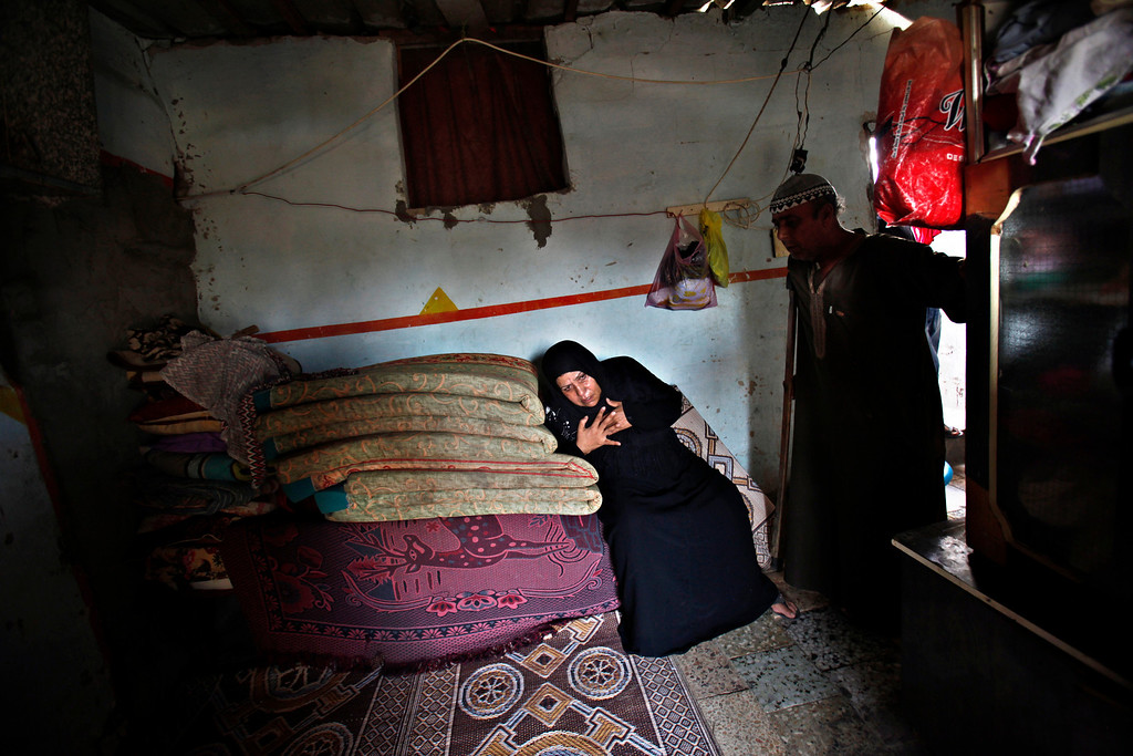 . In this Thursday, Sept. 12, 2013 photo, Palestinian Salih Alwadiya, 61, stands at the door to his home as his wife, Handoma, 54, who suffers from high blood pressure, rests on a pile of mattresses in Gaza City.  ìWhen electricity cuts off, as happens every day, I go to the bed in front of the pigeon cage,î Alwadiya says. ìIn the day, we suffer from flies and at night, we suffer from mosquitoes.î  (AP Photo/Adel Hana)