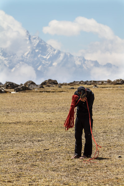 Man standing with climbing rope with snowy mountain in background - Nepal