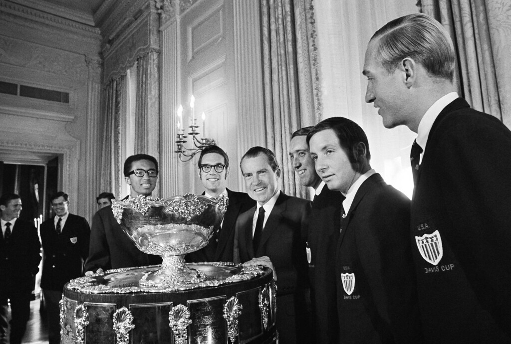 ". U.S. President Nixon bad one word for the huge trophy brought to the White House, Washington, Feb. 11, 1969 by the United States Davis Cup Tennis Team. It was ""Wow\"" The team members with Nixon are, from left: Arthur Ashe, Clark Grachner, Donald Bell and Bob Lutz. They were luncheon guests of Nixon. (AP Photo)"