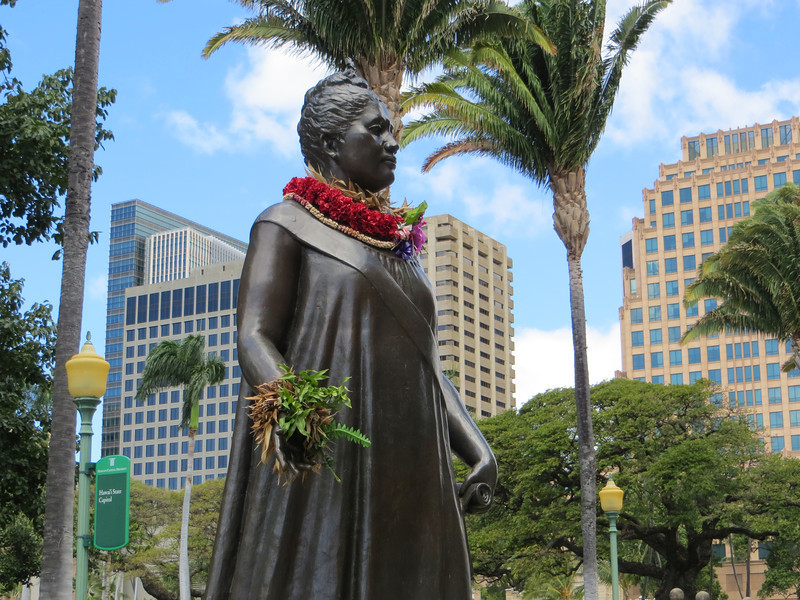 "I did some research to determine what she is holding in her left hand.  I thought it could be either the constitution of 1893 which she wrote herself and tried to ram through the legislature (thus alarming the white powers that be and causing them to get rid of her), or possibly the music to ""Aloha Oe"", which she composed.  My sources said she's supposed to be holding both of them."