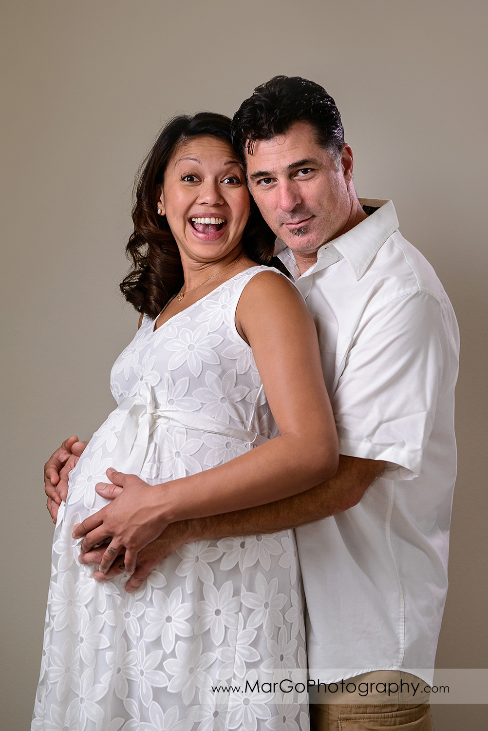 portrait of pregnant woman in white dress and man in white shirt smiling into camera during maternity session