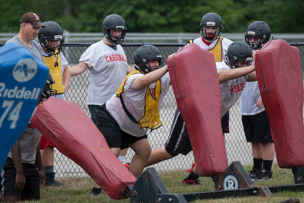 . Jen Forbus - The Morning Journal<br> The Cardinal linemen work on blocking technique at the sled during Brookside\'s first day of football practice on July 30.