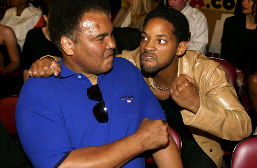 Description of . Boxing legend Muhammad Ali, left, jokes with entertainer Will Smith prior to watching his daughter Laila Ali's bout against Marjorie Jones at the Universal Ampitheatre in Universal City, Calif., Thursday, June 15, 2000.  (AP Photo/Michael Caulfield)