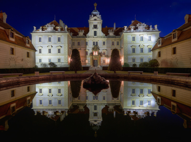 Chateau Valtice  I'm really happy with the composition on this one. It took me 6 tries to get the whole chateau and the whole reflection into one shot. There were just 1-2 pixels between the top of the tower and the end of the photo. I had to add a little bit to the top and bottom, and fill it using content aware, so it's not completely at the border.  I'm not 100% happy with other parts of this photo, as I could really do with a little more brackets, especially few brighter ones. The difference between the brightly lit chateau and the surroundings was just too much for only three shots. Maybe next time :)  In this photo the Chateau in Valtice in Czech Republic. The bottom part is the reflection in the fountain in front of it. It was turned off in the evening, so it was almost like a perfect mirror.  HDR from three shots, taken with Canon 7D with Sigma 10-20mm lens, from a tripod.