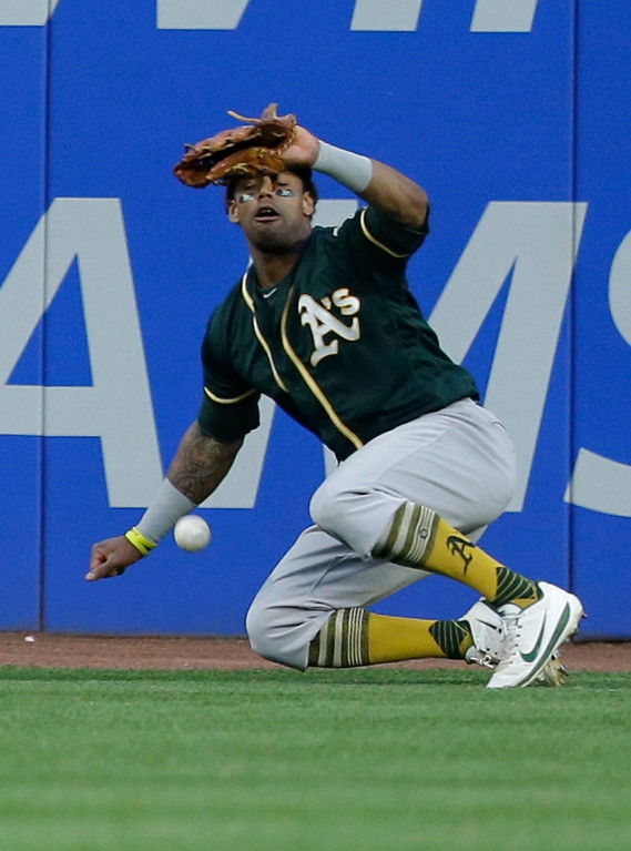 . Oakland Athletics\' Khris Davis can\'t catch a ball hit by Cleveland Indians\' Michael Brantley in the ninth inning of a baseball game, Wednesday, May 31, 2017, in Cleveland. Davis was charged with the error. Brantley was safe at second base. The Athletics won 3-1. (AP Photo/Tony Dejak)