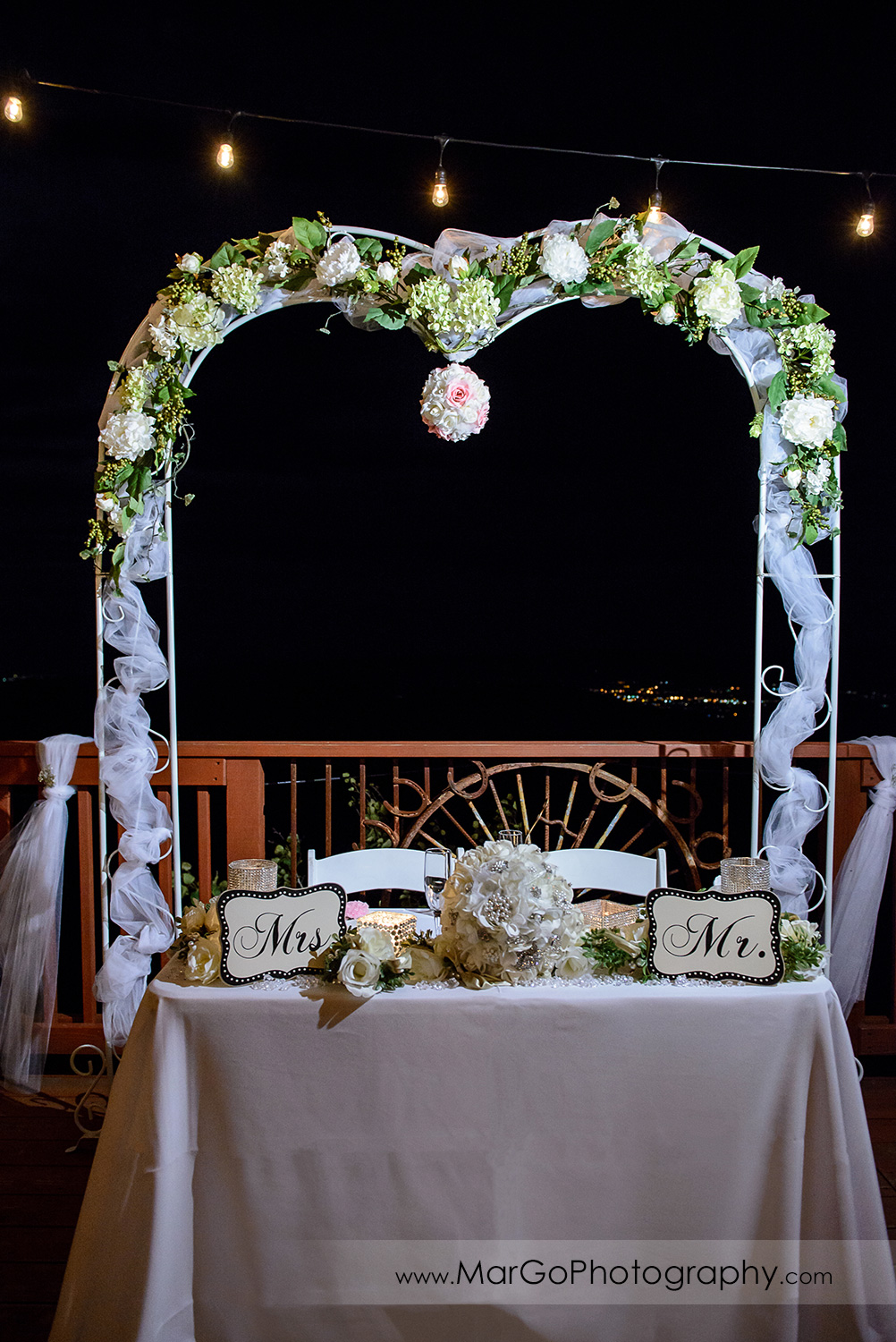 sweetheart table decorated with Mr and Mrs signs and white flower wedding arch