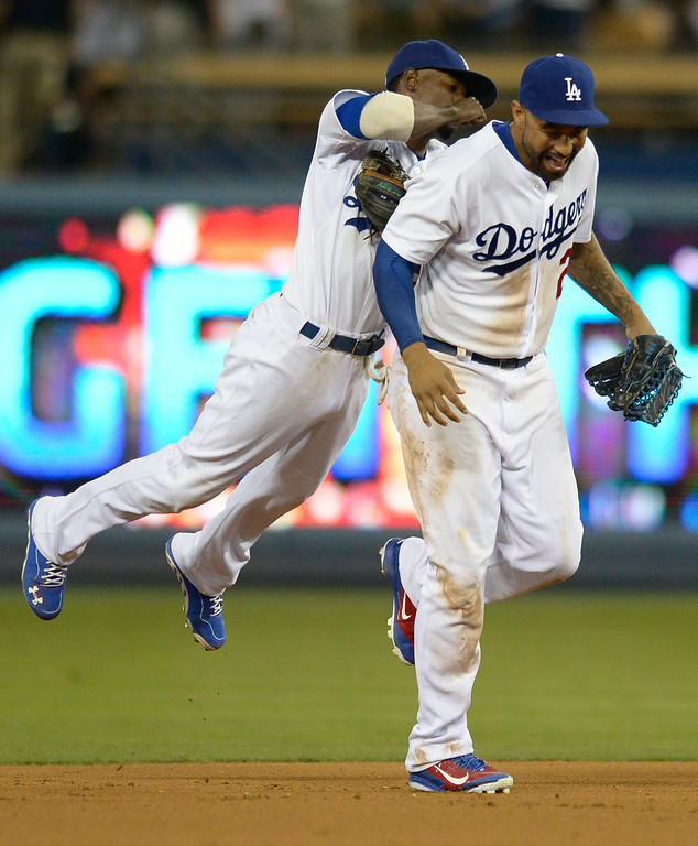 . Dee Gordon jumps on Matt Kemp after the win. The Dodgers defeated the San Diego Padres 8-6 at Dodger Stadium. Los Angeles, CA. 8/19/2014(Photo by John McCoy Daily News)