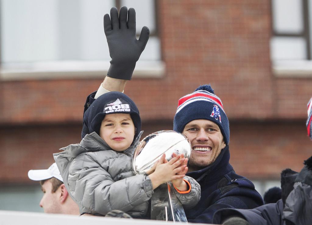 . Benjamin Brady (L) holds the Lombardi trophy as his dad, Patriots quarterback Tom Brady, waves from a duck boat during the New England Patriots victory parade on February 4, 2015 in Boston, Massachusetts. (Photo by Scott Eisen/Getty Images)